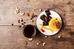 Chocolate candies orange cinnamon coffee and nuts over wooden background. Royalty Free Stock Photography