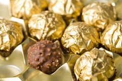 Chocolate candies over golden background Stock Photography