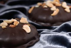 Chocolate candies & peanuts. Milk chocolate candies covered with roasted peanuts. Shallow DOF Stock Image