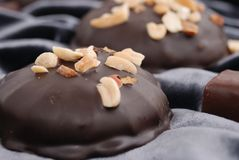 Chocolate candies & peanuts. Milk chocolate candies covered with roasted peanuts. Shallow DOF Royalty Free Stock Image