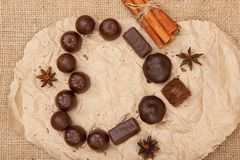 Chocolate candies rectangular and round shape put on pack paper. In the form of a heart with stars anise and cinnamon. Top view stock image