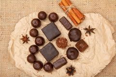 Chocolate candies rectangular and round shape put on pack paper in the form of a heart. With stars anise and cinnamon. Top view stock photography