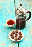 Chocolate Candies on the saucer. A few chocolate candies on the saucer and cup of hot black tea are on wooden table Royalty Free Stock Images