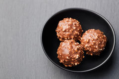 Chocolate candies, truffle in ceramic black bowl on grey slate background Copy space Top view. Chocolate candies, truffle in ceramic black bowl on grey slate royalty free stock photo