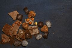 Chocolate, chocolate candies, truffles, cinnamon on a wooden black background. royalty free stock images