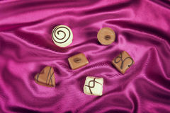Chocolate candies variety on satin background Stock Photo