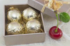 Chocolate candies wrapped in golden coloured packaging in a red. Present box with fresh cherries Stock Images