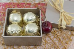 Chocolate candies wrapped in golden coloured packaging in a red. Present box with fresh cherries Royalty Free Stock Photography
