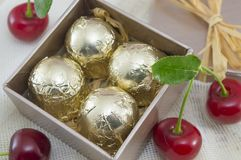 Chocolate candies wrapped in golden coloured packaging in a red. Present box with fresh cherries Stock Image