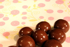 Chocolate candy. Small, chocolate candies on a polka dot background Stock Image