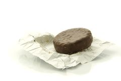 Chocolate candy. On open wrapper against white background Stock Photography