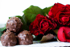 Chocolate candy on background with red roses Royalty Free Stock Photography