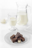 Chocolate candy bird`s milk with air filling. Jug and glass with milk in the background Royalty Free Stock Images