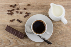 Chocolate candy, coffee beans, coffee in cup, spoon and milk. Chocolate candy, coffee beans, coffee in cup, spoon and jug of milk on wooden table. Top view Royalty Free Stock Photo