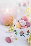 Chocolate candy colored Easter eggs in ceramic cup burning candle, small flowers Royalty Free Stock Photo