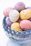 Chocolate candy Easter eggs in pastel colors in blue crystal cup, closeup Stock Image