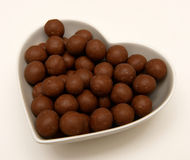 Chocolate Candy in Heart Shaped Bowl. Chocolate malted milk balls candy in heart shaped bowl stock photography