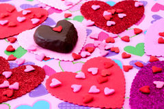Chocolate and candy hearts on heart background Stock Image