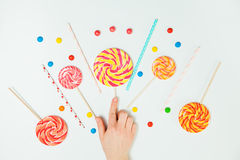 Chocolate Candy Lollipop Hand White Background Lay Flat Pattern. Sweets Composition Stock Photo