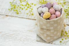 Chocolate candy Multi-Colored Small Quail Easter Eggs Pastel Colors in Linen Sack White Wood Table Yellow Spring Flowers Stock Photos