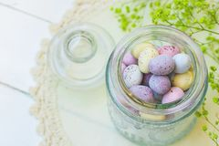 Chocolate Candy Multi-Colored Small Quail Easter Eggs Pastel Colors in Vintage Glass Jar on White Wood Table Yellow Spring Flowers Stock Photos