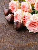 Chocolate candy in the shape of hearts and pink roses for Valentine's day Royalty Free Stock Photography