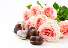 Chocolate candy in the shape of hearts and pink roses for Valentine's day Royalty Free Stock Image