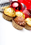 Chocolate candy treats Christmas New Year theme. Chocolate candy treats with Christmas New Year holiday theme ornaments background Stock Photo