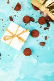 Chocolate Candy truffles fall out. Golden luxury box ad gift on blue background. Copy space, Dessert. Cocoa candies. delicious. tasty. Flat lay royalty free stock photo