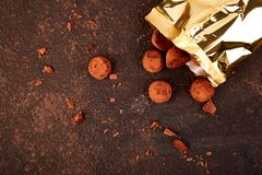 Chocolate Candy truffles fall out. Golden luxury box on  brown background. Copy space, Dessert. Cocoa candies. delicious. tasty. Flat lay Royalty Free Stock Photos