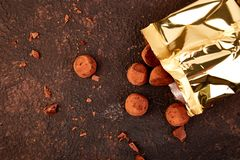 Chocolate Candy truffles fall out. Golden luxury box on brown background. Copy space, Dessert. Cocoa candies. delicious. tasty. Flat lay royalty free stock images