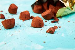 Chocolate Candy truffles fall out. Golden luxury box on blue background. Copy space, Dessert. Cocoa candies. delicious. tasty royalty free stock photo