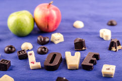 Chocolate candy white and black, heart, figures, two apples and the word love Stock Photo