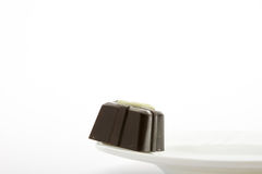 Chocolate candy on white dish, isolated on white background. Close up. Stock Photo