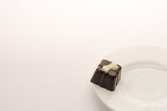Chocolate candy on white dish, isolated on white background. Close up. Royalty Free Stock Photo