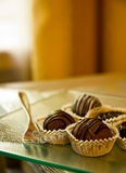 Chocolate candy in wrappers. Pieces of chocolate candy in gold wrappers next to a gold fork Royalty Free Stock Images