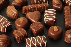 Chocolate candys with icing on dark background. Many chocolate appetizing candys with icing on dark background Stock Images