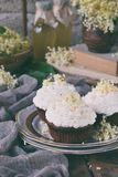 Chocolate capcakes with vanilla cream sprinkled with white chocolate and elderberry flowers. Vintage style. Copy space. stock image