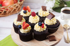 Chocolate capkake with cream and berries, raspberry, strawberry, blueberry, still life, close-up. Chocolate capkake with cream and berries, raspberry, strawberry Royalty Free Stock Photo
