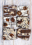Chocolate caramel bark pieces. Assorted chocolate caramel bark pieces for sweet dessert arranged on wooden background, top view Royalty Free Stock Image