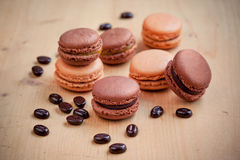 Chocolate and caramel macaroons on wooden table Royalty Free Stock Photography