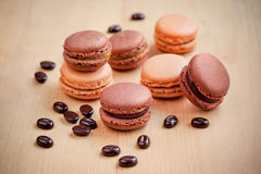 Chocolate and caramel macaroons on wooden table Royalty Free Stock Photo