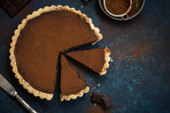 Chocolate and caramel tart on dark blue background. Top view Stock Image