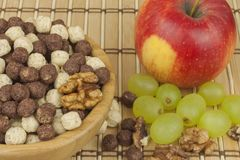 Chocolate cereal balls in a bowl of bamboo. Healthy breakfast with fruit and milk. A diet full of energy and fiber for athletes Royalty Free Stock Photography