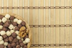 Chocolate cereal balls in a bowl of bamboo. Healthy breakfast with fruit and milk. A diet full of energy and fiber for athletes Royalty Free Stock Images