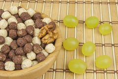 Chocolate cereal balls in a bowl of bamboo. Healthy breakfast with fruit and milk. A diet full of energy and fiber for athletes Stock Images