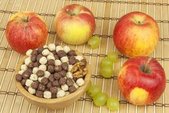 Chocolate cereal balls in a bowl of bamboo. Healthy breakfast with fruit and milk. A diet full of energy and fiber for athletes Stock Photos