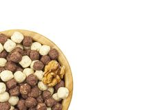 Chocolate cereal balls in a bowl of bamboo. Healthy breakfast with fruit and milk. A diet full of energy and fiber for athletes. Stock Photo