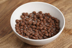 Chocolate cereal balls with milk in white bowl for breakfast on wooden table Stock Photo