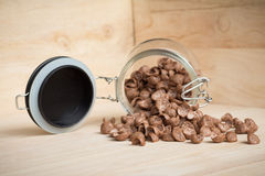 Chocolate cereal cornflakes spilling to the wood surface Stock Photos